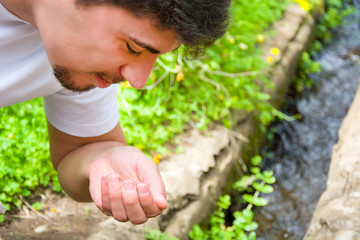 Man drinking water from the stream