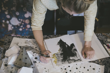 Artist drawing with gold marker