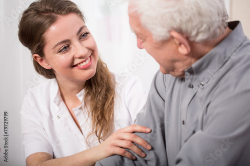 Smiling nurse assisting senior man - 79729799