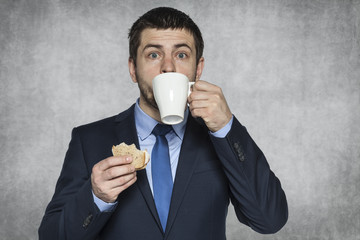 hungry businessman eating a sandwich