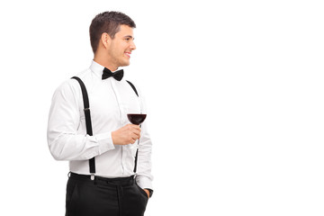 Cheerful young man holding a glass of red wine