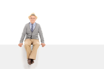 Cheerful senior gentleman sitting on a blank panel