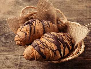 Crispy fresh croissants in a basket on a wooden table