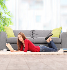 Young woman reading book and lying on the floor
