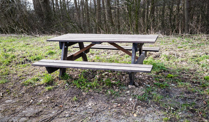Empty wooden picnic bench and table in the roadside at the fores