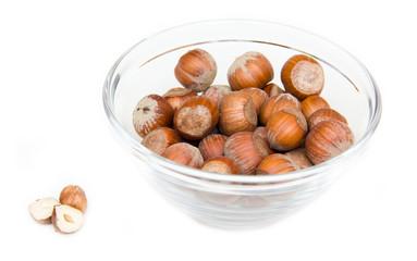 Hazelnuts on glass bowl on white background