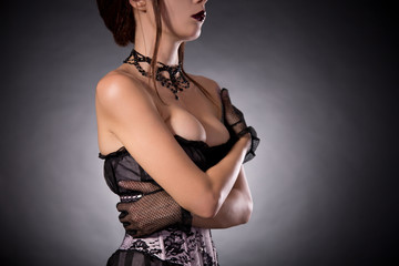 Busty woman in Victorian corset embracing herself