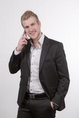 Junger Geschäftsmann telefoniert und lächelt