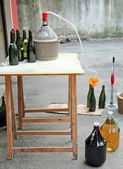 bottling red wine in glass bottles with an orange funnel
