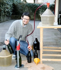 man pour red wine from the demijohn to glass bottles