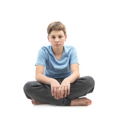 Tired young boy sitting in a lotus position