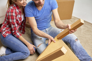 close up of couple unpacking furniture and moving