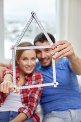 close up of couple with house shape ruler