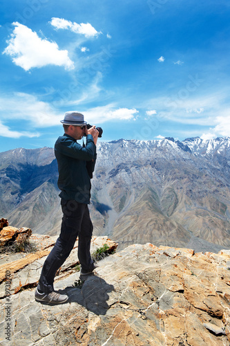 Poster photographer tourist in mountains