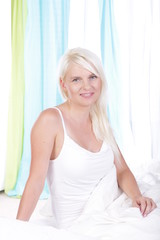 Blonde junge Frau im Bett