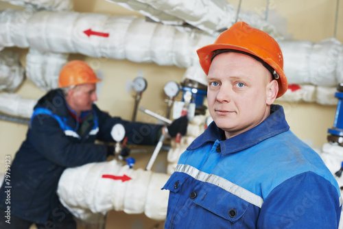heating engineer repairmans in boiler room - 79739123
