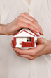Miniature model house in woman's hands
