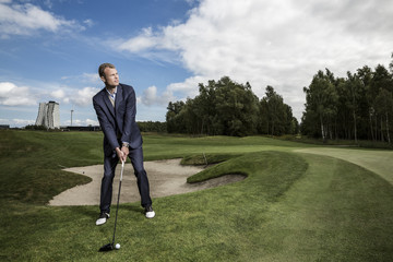 Young handsome business man playing golf outdoors