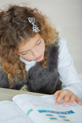 Little girl reading through a textbook