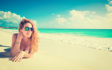 Smiling beautiful woman with sunglasses sunbathing on a beach