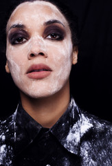 beautiful mulatto with flour on her face a black background