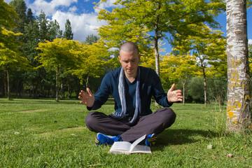 Joven con un Libro en un Parque y gesticulando con las manos
