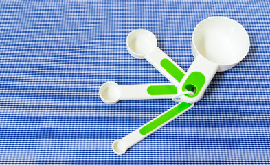 Set of Measuring Spoon with Green Handle Placed on Blue Scotch B
