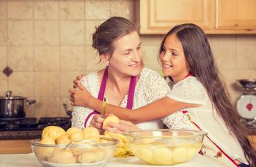 happy, smiling mother daughter cooking dinner preparing food