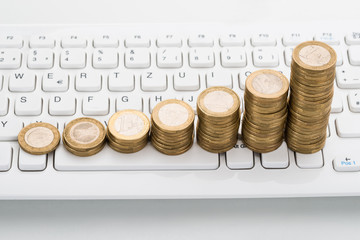 Stack Of Coins On Keyboard