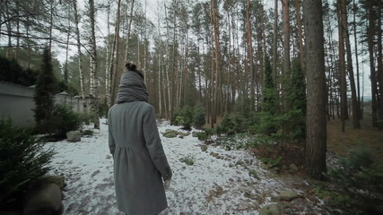 A girl walking along the wall in a winter forest