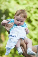 Women's hands holding newborn baby..