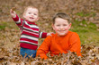 Brothers playing in leaves outdoors during autumn