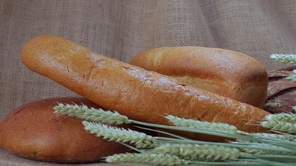 Showcase of different varieties of bread with wheat spikelets