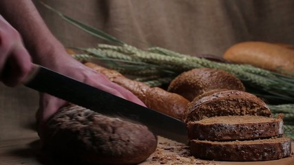 Cutting of black bread on the bread table.