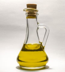 Vegetable oil in a bottle decanter on a white background