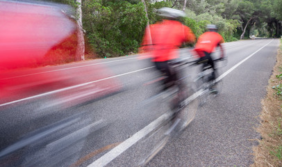 Blurred Cyclists and road