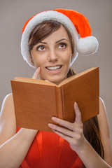 smiling woman in Santa Claus clothes with book
