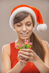 smiling woman in Santa Claus clothes with flower