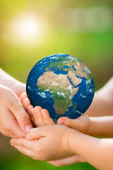 Children holding Earth planet in hands