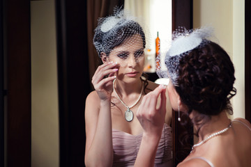 Beautiful lady in veil is looking at the mirror.