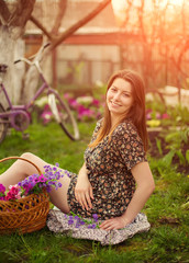Beautiful young woman in dress sitting on grass with basket of f