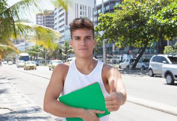 Sportlicher Student auf der Strasse zeigt den Daumen