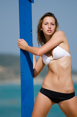 Fitness model with bikini is leaning against a blue pillar