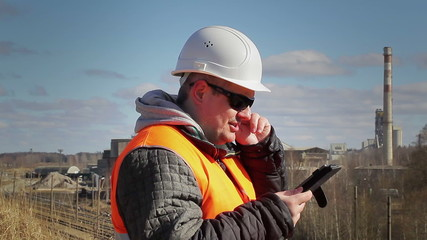 Engineer talking on the cell phone near factory