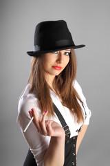 beautiful young woman in hat smoking cigarette in studio grey ba