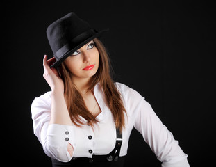 beautiful young woman in hat in studio black background