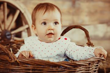 Little girl sitting in a wicker basket