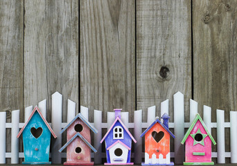 Row of colorful birdhouses by white picket fence