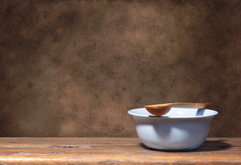 Blue bowl and wooden spoon on brown grunge background