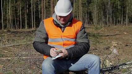 Lumberjack counting euro banknotes in forest